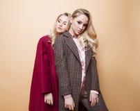 adatti un ritratto di due ragazze, posa dei migliori amici dell'interno sul cappotto alla moda d'uso dell'inverno del fondo beige fotografia stock libera da diritti