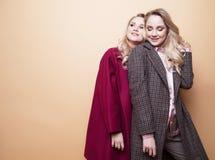 adatti un ritratto di due ragazze, posa dei migliori amici dell'interno sul cappotto alla moda d'uso dell'inverno del fondo beige immagini stock