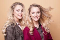 adatti un ritratto di due ragazze, posa dei migliori amici dell'interno sul cappotto alla moda d'uso dell'inverno del fondo beige fotografia stock