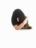 Adavanced contorted yoga pose. Young woman in yoga pose, face invisible, body side view, dressed in black, on white background royalty free stock photos