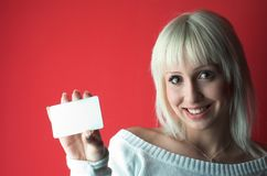 Add. Put your message on blank card. Attractive blond girl over red background Royalty Free Stock Images