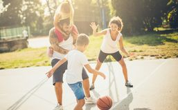 Add the ball and let your team win. Family playing basketball royalty free stock photo