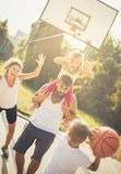 Add the ball to the player. Family playing basketball royalty free stock image