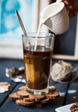 Add cream to black coffee cup, hand Stock Photo