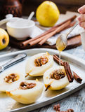 Add honey to a pear with walnuts, cinnamon sticks, cooking proce Stock Photos