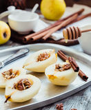 Add honey to a pear with walnuts, cinnamon sticks, cooking proce Stock Photo