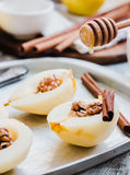 Add honey to a pear with walnuts, cinnamon sticks, cooking proce Stock Image