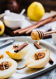 Add honey to a pear with walnuts, cinnamon sticks, cooking proce Royalty Free Stock Image