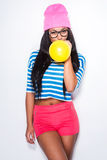 Add some colors!. Beautiful young African woman in funky clothes blowing yellow balloon and looking at camera while standing against white background stock images