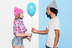 Add some colors. Handsome young African men giving a blue balloon to his girlfriend while standing against colorful background Royalty Free Stock Photo