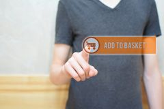 Add to basket - man hand pressing button. Add to basket - man hand pressing transparent orange virtual interface button with cart icon on grunge light brown stock images