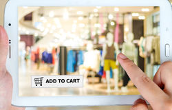 Add to cart on tablet screen, business, E-commerce. Add to cart over blur store background on tablet screen, business, E-commerce, on line shopping background royalty free stock photo