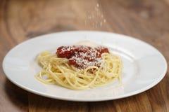 Add zerrieb Parmesankäse auf Spaghettis Bewohner von Bolognese Stockbild