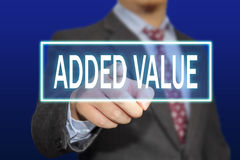 Added Value Concept. Business concept image of a businessman clicking Added Value button on virtual screen over blue background royalty free stock photo