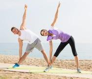 Addestramento allegro della donna e dell'uomo sulla spiaggia dal mare Fotografia Stock Libera da Diritti