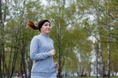 Addestramento ambulante della donna di potenza nella sosta Bello modello sportivo di forma fisica durante l'allenamento all'apert Fotografia Stock