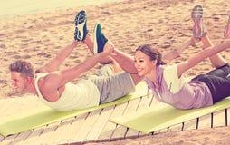 Addestramento amichevole della donna e dell'uomo sulla spiaggia dal mare Fotografie Stock
