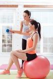Addestramento atletico della donna due con il fitball e le teste di legno Fotografia Stock