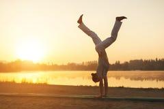 Addestramento atletico di allenamento dell'esecutore di capoeira sui sunris della spiaggia Fotografia Stock