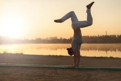 Addestramento atletico di allenamento dell'esecutore di capoeira sui sunris della spiaggia Immagini Stock