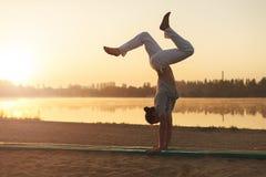 Addestramento atletico di allenamento dell'uomo di yoga sull'alba della spiaggia Fotografia Stock