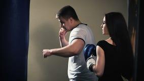 Addestramento castana sveglio della donna con i guantoni da pugile alla palestra stock footage