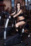 Addestramento d'uso degli abiti sportivi della giovane donna muscolare sulle bici di esercizio in palestra Cardio allenamento int Immagine Stock