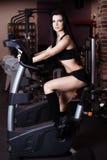 Addestramento d'uso degli abiti sportivi della giovane donna muscolare sulle bici di esercizio in palestra Cardio allenamento int Fotografia Stock