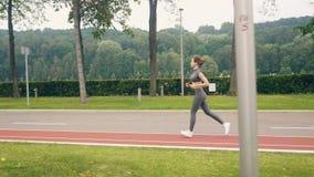 Addestramento del corridore della giovane donna nel parco di estate Addestramento di forma fisica e di sport stock footage