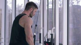 Addestramento del culturista, tipo di sport che fa allenamento della costruzione del muscolo sul simulatore della trazione mentre stock footage