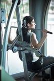 Addestramento del peso della donna alla ginnastica L'esercitazione sopra tira giù la macchina del peso Donna che fa tirata-UPS ch Fotografia Stock