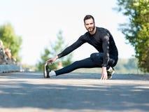 Addestramento dell'uomo che allunga dopo l'allenamento in natura Immagine Stock