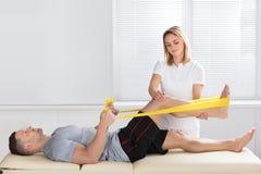 Addestramento dell'uomo con la banda di esercizio assistita dal fisioterapista fotografia stock