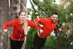 Addestramento dell'uomo e della donna di sport nel parco Immagini Stock Libere da Diritti