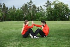Addestramento dell'uomo e della donna di sport nel parco Immagine Stock