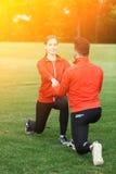 Addestramento dell'uomo e della donna di sport nel parco Immagini Stock