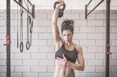 Addestramento della donna con le campane del bollitore Fotografie Stock