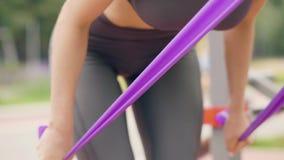 Addestramento della donna di forma fisica con l'estensore di sport nella fine del parco di estate su video d archivio