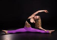 Addestramento della donna di forma fisica nello studio scuro Allungamento della ragazza Fotografie Stock Libere da Diritti