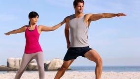 Addestramento della donna e dell'uomo sulla spiaggia stock footage