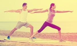 Addestramento della donna e dell'uomo sulla spiaggia dal mare Immagine Stock
