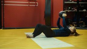 Addestramento della donna nella palestra - dallo stare alla posizione seduta con la palla archivi video