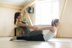Addestramento della giovane donna con l'istruttore privato di yoga nella classe di yoga Immagini Stock Libere da Diritti
