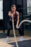 Addestramento della giovane donna con le corde nella palestra di CrossFit Immagini Stock