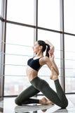 Addestramento della giovane donna nel asana di yoga - posa del piccione contro la finestra nello studio di forma fisica Fotografie Stock Libere da Diritti
