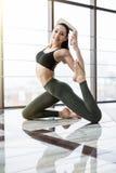 Addestramento della giovane donna nel asana di yoga - posa del piccione contro la finestra nello studio di forma fisica Immagine Stock Libera da Diritti