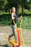 Addestramento della giovane donna sul costruttore del muscolo Fotografia Stock