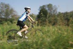 Addestramento della giovane donna sul mountain bike e ciclare nel parco fotografia stock