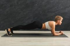 Addestramento della plancia della donna di forma fisica al fondo grigio all'interno Immagine Stock Libera da Diritti