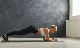 Addestramento della plancia della donna di forma fisica al fondo grigio all'interno Fotografie Stock Libere da Diritti